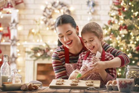 Merry Christmas and Happy Holidays. Family preparation holiday food. Mother and daughter cooking cookies. Reklamní fotografie - 90084627