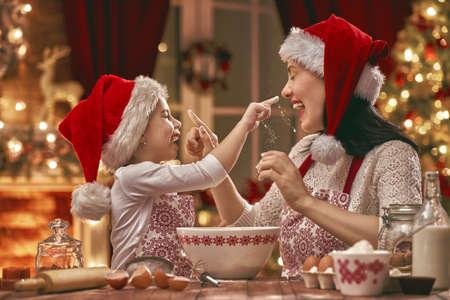 Feliz Navidad y Felices Fiestas. Preparación de la familia comida de vacaciones. Madre e hija cocinando galletas. Foto de archivo