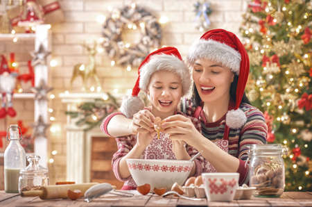 Merry Christmas and Happy Holidays. Family preparation holiday food. Mother and daughter cooking cookies. Stok Fotoğraf - 90084631