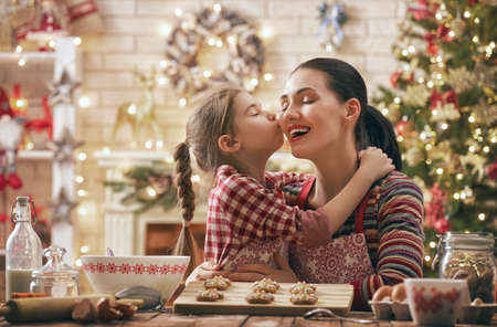 christmastime: Merry Christmas and Happy Holidays. Family preparation holiday food. Mother and daughter cooking cookies.