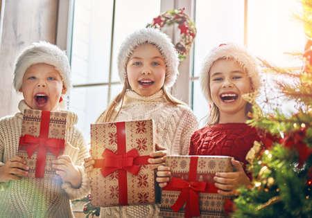 Joyeux Noël et joyeuses fêtes! Joyeux enfants mignons ouverture des cadeaux. Les enfants s'amusent près de l'arbre le matin. Famille aimante avec des cadeaux dans la chambre. Banque d'images - 90145784