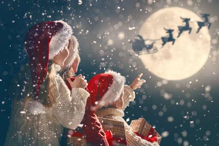 Frohe Weihnachten und schöne Feiertage! Nette kleine Kinder mit Weihnachtsgeschenken. Santa Claus-Fliegen in seinen Pferdeschlitten gegen Mondhimmel. Kinder, die den Feiertag mit Geschenken auf dunklem Hintergrund genießen.