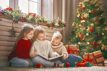 Merry Christmas and Happy Holiday! Cute little children reading the book near tree at home.