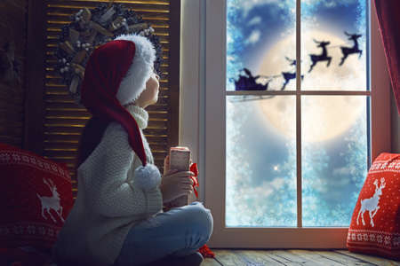 Cute little child girl sitting by window and looking at Santa Claus flying in his sleigh against moon sky. Room decorated on Christmas. Kid enjoy the holiday.