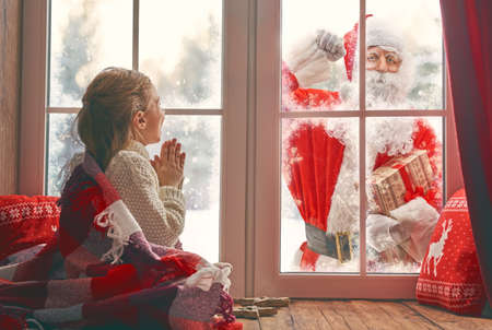 Cute little child girl is sitting by window and looking at Santa Claus knocking at home. Room decorated on Christmas. Kid enjoy the holiday.