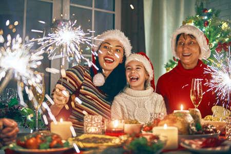 Joyeux Noël! Une famille heureuse dîne à la maison. Vacances de célébration et convivialité près d'arbre.