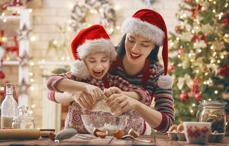 Merry Christmas and Happy Holidays. Family preparation holiday food. Mother and daughter cooking cookies. Imagens - 90521493