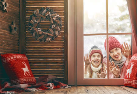 Happy loving family! Mother and child girl having fun, playing and laughing on snowy winter walk in nature. Frost season. Child and mom looking in windows, standing outdoors. View indoors home.