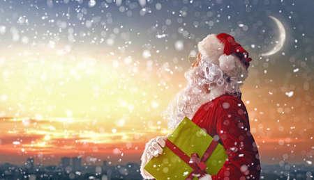 Merry Christmas and happy holidays! Santa Claus looking at city.