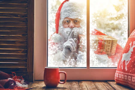 Merry Christmas! Santa Claus is knocking at window. Room decorated for holidays. View indoors home. Stock Photo