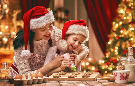 Merry Christmas and Happy Holidays. Family preparation holiday food. Mother and daughter cooking cookies.