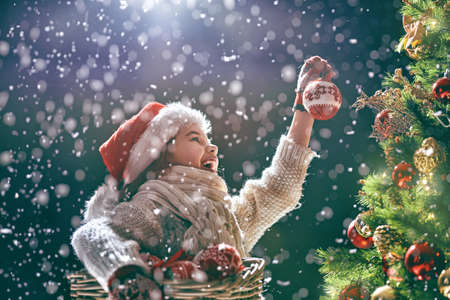 Merry Christmas and Happy Holidays! Cute little child decorating the tree outdoors. Xmas night.