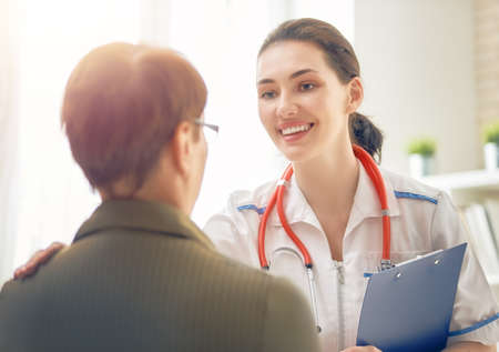 Female patient listening to doctor in medical office. Stock Photo