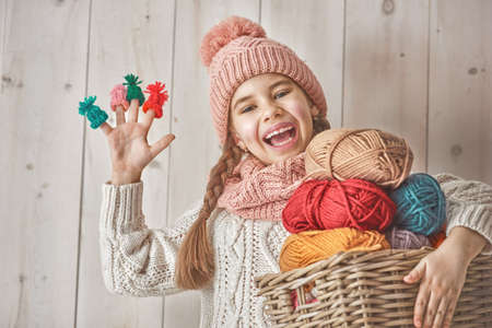 Winter portrait of happy little girl wearing knitted hat, scarf and sweater. Child holding a basket of skeins of yarn and having small hats on her fingers on white wooden background. Family fashion concept.