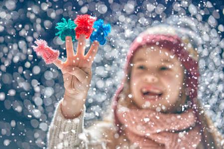 겨울 초상화 니트 모자, 스카프와 스웨터를 입고 행복 한 작은 소녀의. 어두운 눈 덮인 배경에 그녀의 손가락에 작은 모자 데 아이. 가족 패션 개념입니 스톡 콘텐츠