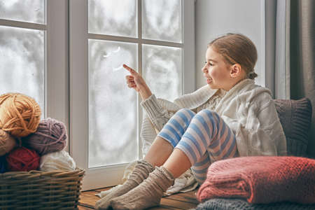 Cute little girl sitting by the window and drawing smile on frozen glass. Kid enjoys the winter.