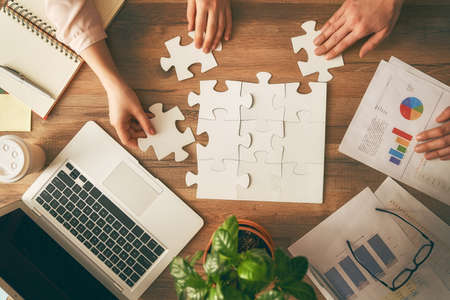 Man and woman working in the office. Collaborative teamwork. People are trying to connect couple puzzle piece. Symbol of association and connection. Concept of business strategy. Reklamní fotografie