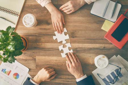 Man en vrouw die op kantoor werken. Collaboratief teamwerk. Mensen proberen een paar puzzelstukjes te verbinden. Symbool van associatie en verbinding. Concept van bedrijfsstrategie.