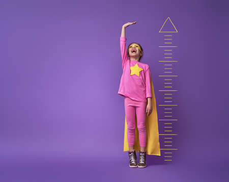 Little child is playing superhero. Kid is measuring the growth on the background of bright ultraviolet wall. Girl power concept. Yellow, pink and  purple colors. Archivio Fotografico