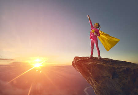 Little child girl is playing superhero. Child on the background of sunset sky. Girl power concept
