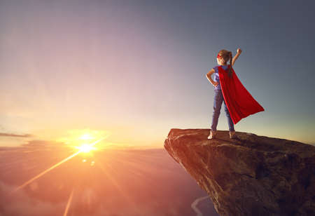 Little kid is playing superhero. Child on the background of sunset sky. Girl power concept 스톡 콘텐츠
