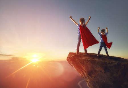 Deux petits enfants jouent au super héros. Enfants sur fond de ciel coucher de soleil. Concept de pouvoir de fille
