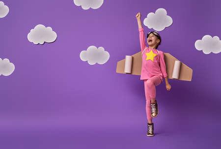 Kleines Kindermädchen in einem Astronautenkostüm spielt und träumt davon, ein Raumfahrer zu werden. Porträt des lustigen Kindes auf einem Hintergrund der ultravioletten Wand mit weißen Wolken.