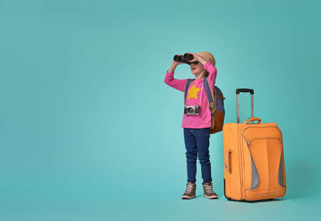 Dreams of travel! Child with suitcase and binoculars on background of bright blue wall. Stock Photo