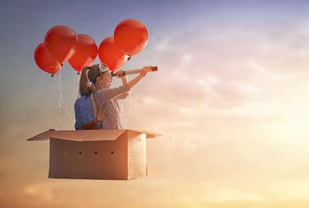Dromen van reizen! Kind vliegt in kartonnen doos met luchtballonnen. Stockfoto
