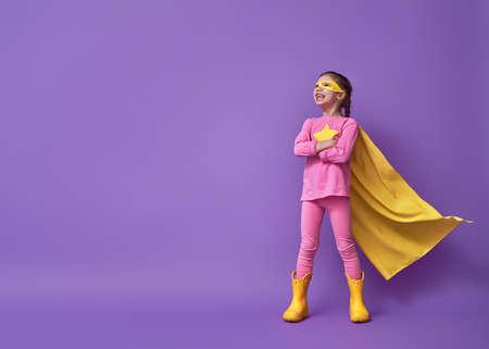 Małe dziecko bawi się superbohaterem. Dziecko na tle jasnej ściany ultrafioletowej. Koncepcja mocy dziewczyny. Kolory żółty, różowy i fioletowy. Zdjęcie Seryjne