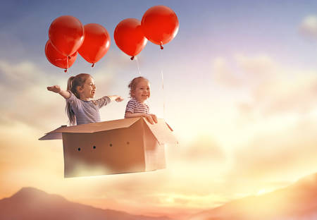 Dreams of travel! Two children are flying in cardboard box with air balloons. Stock fotó