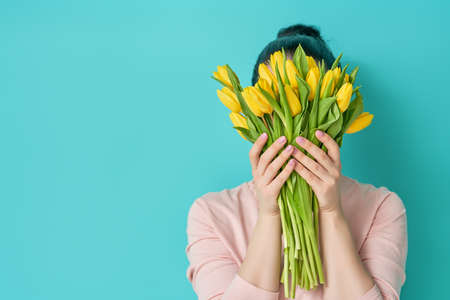 Beautiful young woman in the pink dress with yellow flowers tulips in hands on light blue background. Reklamní fotografie