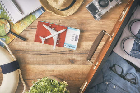 Go on an adventure! The map, suitcase, passports, tickets and the camera on a wooden table. Top view.