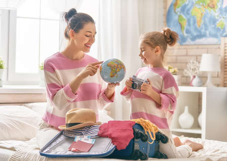 Go on an adventure! Happy family preparing for the journey. Mom and daughter are packing suitcases for the trip. Stock Photo