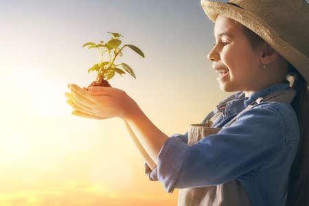 Nettes kleines Kindermädchen mit Sämlingen auf Sonnenunterganghintergrund. Lustiger kleiner Gärtner. Frühlingskonzept, Natur und Pflege.
