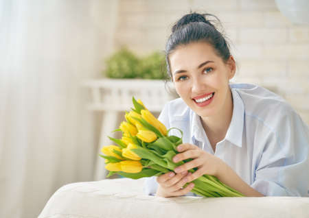 Beautiful young woman in the blue dress with flowers tulips in hands on bed at home.