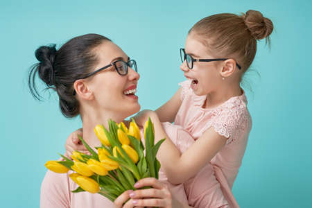 Happy women's day! Child daughter is congratulating mom and giving her yellow flowers tulips. Mum and girl smiling and hugging on light blue background. Family holiday and togetherness.