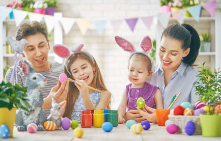 Mother, father and daughters are painting eggs. Happy family are preparing for Easter. Cute little children girls wearing bunny ears. Banque d'images
