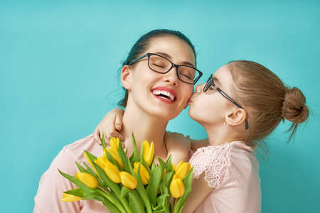 Happy womens day! Child daughter is congratulating mom and giving her yellow flowers tulips. Mum and girl smiling and hugging on light blue background. Family holiday and togetherness.