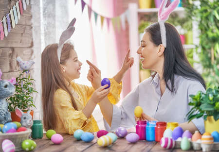 Happy holiday! A mother and her daughter are painting eggs. Family preparing for Easter. Cute little child girl is wearing bunny ears. Banco de Imagens - 96208873
