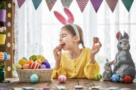 Beautiful child is eating chocolate eggs. Happy family preparing for Easter. Cute little girl is wearing bunny ears.