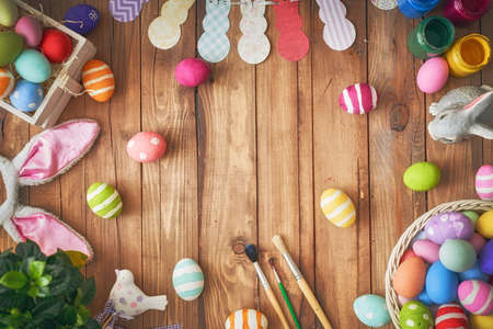 Happy Easter! Background with colorful eggs in basket. Table decorating for holiday. Top view.