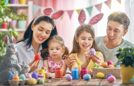 Mother, father and daughters are painting eggs. Happy family are preparing for Easter. Cute little children girls wearing bunny ears. Stock Photo - 96915649