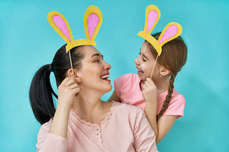 Family are celebrating Easter. Mother and her cute daughter with paper bunny ears on sticks on bright light blue background.