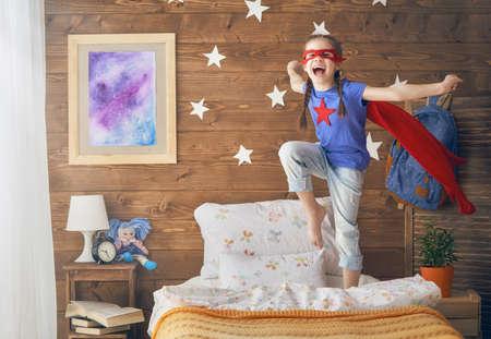 Little child playing superhero in the kids room. Girl power concept. Stock fotó