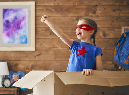 Little child playing superhero in the kids room. Girl power concept.