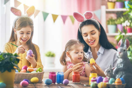 Happy holiday! A mother and her daughters are painting eggs. Family preparing for Easter. Cute little children girls are wearing bunny ears. Stock Photo