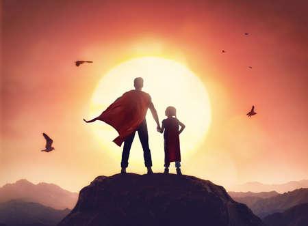 Glückliche liebevolle Familie. Vater und seine Tochter spielen im Freien. Papa und sein kleines Mädchen in den Kostümen eines Superhelden.