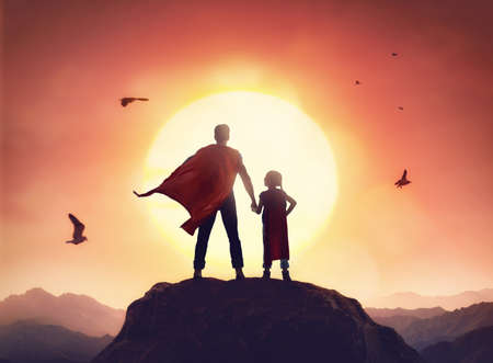 Happy loving family. Father and his daughter playing outdoors. Daddy and his child girl in an Superhero's costumes. Stock Photo