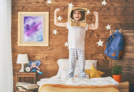 Child girl in an astronaut costume is playing and dreaming of becoming a spacemen. Portrait of funny kid in the bedroom.